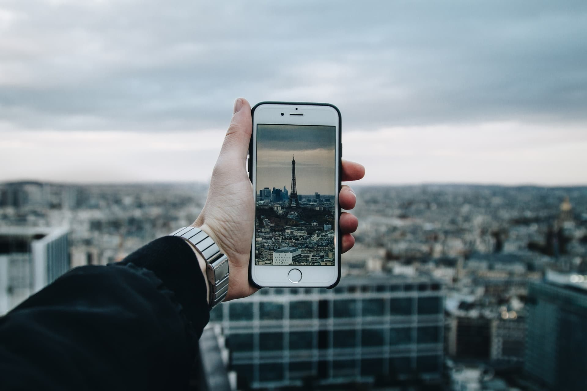 Iphone being held up over the city of Paris.